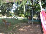Une partie de l'espace jeux avec table ping-pong, balançoires, trapèze, maisonnette en bois.......