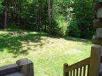 The backyard at Hilltop View Lodge boasts a fire pit and access to walking trails in the woods.