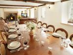 The dining area has seating for 18 at an antique table with linen table cloths and napkins provided