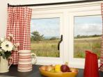 Peep out from the kitchen over the fields to the coast of Dinas Head and Newport beyond
