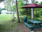 Picnic table and umbrella next to charcoal grill and horseshoe pit for some added fun