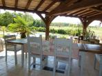 dinning area with seating for 12 covered terrace with views of meadow and swimming pool