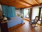 El dormitorio con las ventanas grandes y el suelo de madera.
