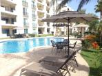 One of two pools with Chaise lounge chairs, umbrellas, tables & chairs