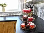 Yummy cakes on cake stand in large newly fitted well equipped modern  kitchen.