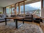 Lounge of the apartment features panoramic windows offering spectacular mountain vews