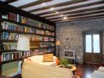 Amplio salón estilo rústico con librería y sofás para el descanso.