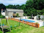 The outdoor heat swimming pool, sun terrace with loungers and barbecue, and the children's play