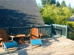 Private sunny backyard deck with lounge chairs, gas BBQ and lovely forest views