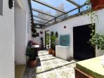 Beautiful covered patio with Spanish tiles and doors through to the garden terrace