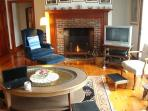 Open living area, seating 6 comfortably, with working fireplace, large coffee table and television
