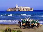 courses de Touaregs sur la plage avec vue sur le fort en pleine mer à Agadir