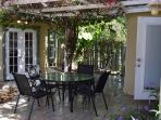 Dining alfresco under the trellis between the main house and studio