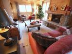 Spacious, comfortable lounge area arranged around the open log fire
