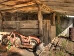 Old Puch motor bike in shed, near cottages.