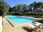 La piscine sécurisée par portillons,  entourée d'arbres. Avec table à l'ombre et barbecue.