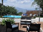 Lounges, terrace and pool with views of Mount Vesuvius
