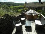 The decked area has a rattan suite, ideal for relaxing with a glass of wine and enjoying the views