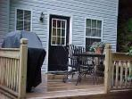 Wrap around porch leads to BBQ and seating for 6-7 people,,in front of stream.