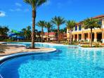 Beautiful pool surrounded by palm trees, clubhouse and poolside snack bar