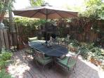 Al fresco dining in beatifully planted courtyard with fountain and shade trees