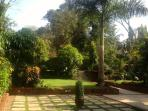 The front formal terraces contrast with 1.5 acres of lush sub-tropical flora in the enormous garden