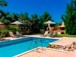 Pool area with sun loungers and umbrellas