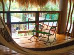 Hammock and locally-made rocking chair offer a relaxing pool view in the comfort of the river breeze