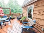 Deck has gas grill, outdoor table and chairs, benches, and adirondack chairs