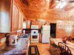 View from back deck to kitchen/dining room, high beams, knotty pine walls and ceiling, wood floor
