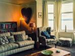 Sitting room with large bay window offering panoramic sea views across the Clyde