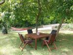 Zona relax debajo de los árboles con mesa y hamacas
