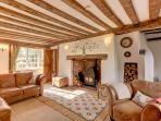 Cosy sitting room with large inglenook and wood burner..