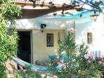 L'entrée de la maisonnette avec la terrasse, les voiles d'ombrage et le hamac