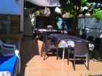 jardin con dos mesas grandes , barbacoa de leña y carbon, con banco