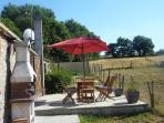 Terrasse privative avec salon de jardin, parasol, barbecue et superbe vue sur la campagne