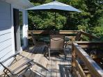 The deck has a dining set with umbrella and deck chairs.