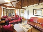 Spacious lounge with vaulted ceilings and woodburner