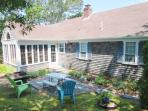 Exterior- Back of seaside cottage with patio and charcoal bulit in grill and small table - 11 Marshview Road Chatham...