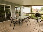 The covered, screened in back porch has a BBQ and patio furniture for outdoor dining and relaxing.