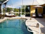 Wicker Chaise Lounges with pool and patio