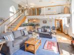 Spacious living area with double height ceiling, gothic-arched windows and woodburner.