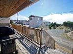 West facing deck with a bench, gas BBQ and ocean views