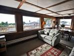 Lower level living room with a flat screen TV/VCR/DVD, wood stove, additional dining table for 5 and ocean views