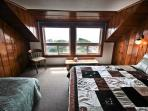 Upper level master bedroom with a Queen and Twin bed with ocean views