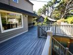 Large upper entry deck with a patio table, chairs and a charcoal BBQ.