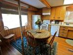 Fully equipped kitchen with all appliances and dining table for six.