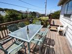 Upper south facing wrap around deck with patio table and chairs and a charcoal BBQ