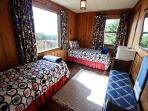 Upper level fourth bedroom with two Twin beds, beautiful ocean views and a bench seat.