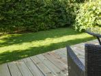 Seating area in garden on wooden decking.